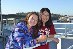 UW undergraduate students Jessie and Diana happy to be onboard the R/V Thompson as we depart Seattle for the Ocean Observatories Initiative Cabled Array cruise 2015. Credit: Mitch Elend, University of Washington.