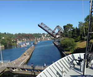 Under beautiful blue skies, the R/V Thompson prepares to exit the Ballard Locks to begin the Cabled Array VISIONS'15 expedition as part of NSF's Ocean Observatories Initiative. Photo Credit: D. Kelley, University of Washington.