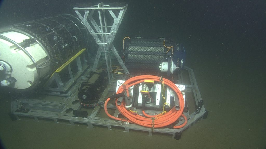 The cabled coastal surface-piercing profiler (cCSPP) was delivered to the seafloor by ROPOS and placed roughly 12 meters due East of the medium-powered junction box MJ01C at the Oregon Shelf site, in 79 meters of water. The cylindrical sensor pod of the cCSPP (left side of image) will float freely in the water column after being released from the deployment cradle on the profiler base. Once powered up, the sensor pod will move up and down in the water column at least 4 times per day, taking samples continuously using the onboard CTD, oxygen, fluorometer, nitrate, AC-S, PAR sensor, spectral irradiance, and 3D water velocity sensors.    Photo Credit: NSF/UW/CSSF, Dive R1801, V14