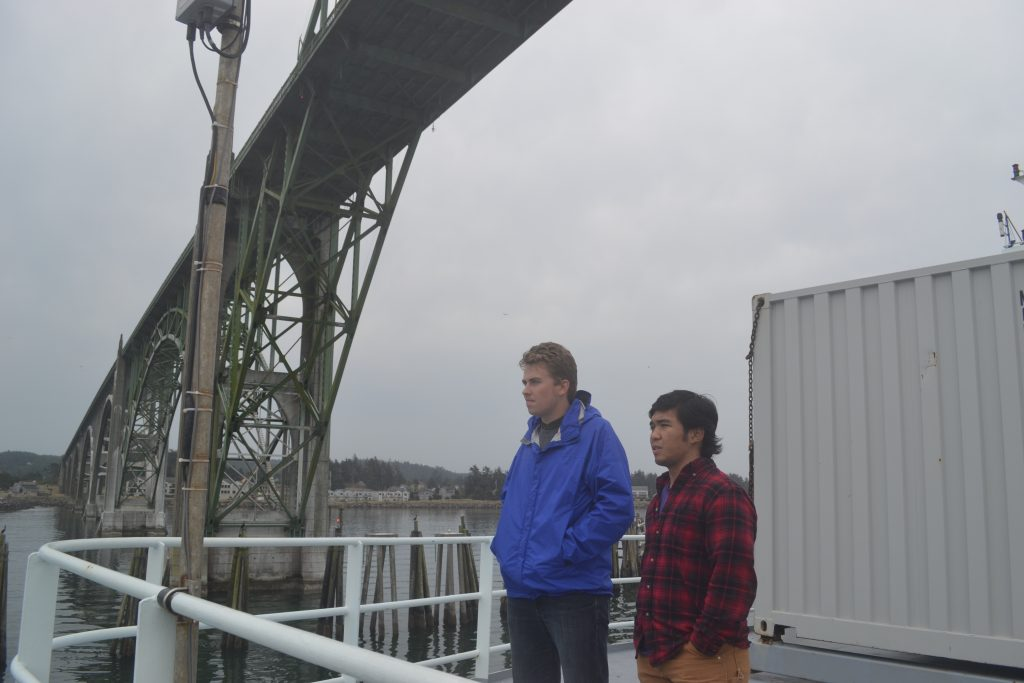 Students, Max Schrempp (left) and Jae Jose look on as the Thompson passes under the Yaquina Bay Bridge on the way in to Newport.  Credit: Mitch Elend