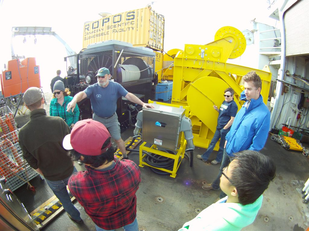Skip Denney provided the students of Leg 5 a tour of the fantailwhich included a detailed explanation of all of the parts to the vertical moorings anda descriptrion of the equipmentutilized in the deployment of it.  Photo Credit: Colin Katagiri, University of Washington, V14