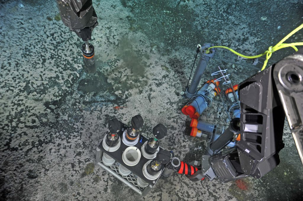 """A push core is taken with the ROV ROPOS adjacent to an OOI-RSN """"Mosquito"""" flow meter built by E. Solomon at the University of Washington. The entrapped sediment, pore fluids, and bacterial mats were brought back to the ship for ship- and shore-based analyses. Photo credit: NSF-OOI/UW/CSSF; Dive R1772; V14."""
