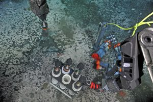 "A push core is taken with the ROV ROPOS adjacent to an OOI-RSN ""Mosquito"" flow meter built by E. Solomon at the University of Washington. The entrapped sediment, pore fluids, and bacterial mats were brought back to the ship for ship- and shore-based analyses. Photo credit: NSF-OOI/UW/CSSF; Dive R1772; V14."