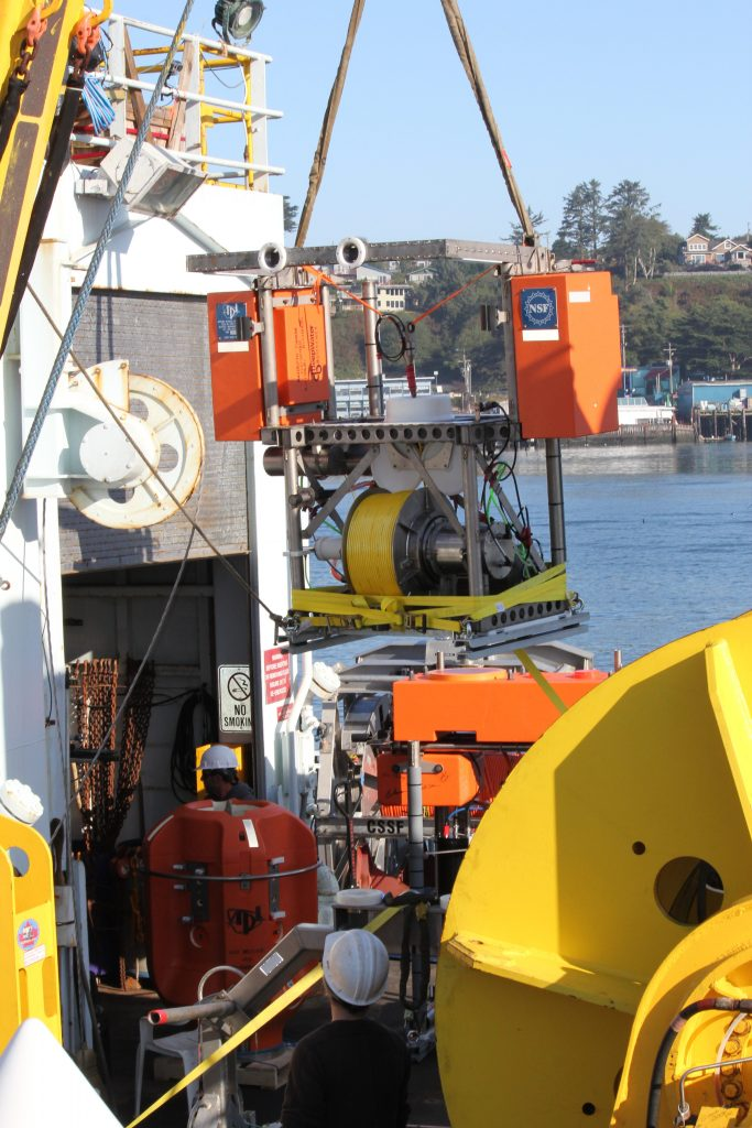 """During the port call for Leg 4 in Newport, Oregon, the UW-APL-built Shallow Winched Profiler was loaded onto the R/V Thompson. The system has an underwater level wind that """"spools"""" out yellow cable, which will provide power and communications to an attached instrument """"pod"""" (orange bulbous-shaped package bottom left). The profiler will be located at a water depth of ~197 m on the already installed mooring at the EA Offshore Site. Several times a day the instrument pod will rise from the 197-m-deep platform to just beneath the ocean's surface making critical chemical and biological measurements. Photo Credit: Skip Denny, APL-UW; V14."""
