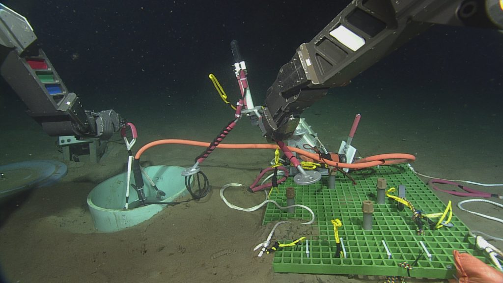 ROPOS lowering the Slope Base seismometer into the previously excavated caisson. After deployment, the caisson was filled with glass beads to couple the seismometer to the seafloor. The attached hydrophone tripod is being held in the starboard arm of ROPOS, and was deployed alongside.  Photo Credit: NSF-OOI/UW/CSSF, Dive R1751, VISIONS14