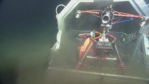 The digital stil camera in the ROPOS toolbasket during deployment at Endurance Oregon Offshore site (600 m). Unlike the cameras placed at Axial Volcano, the camera at Endurance Offshore is designed to look at the seafloor in general, observing animal activity, sediment transport, detritus falls, and bioturbation.  	Photo Credit: NSF-OOI/UW/CSSF, Dive 1747, V14
