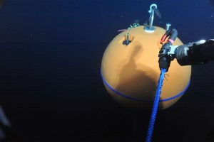 ROPOS attaching a line to the flotation sphere at the top of the deep profiler mooring at Axial Base, prior to recovery to fix a connector problem.  	Photo Credit: NSF-OOI/UW/CSSF, Dive 1740, V14