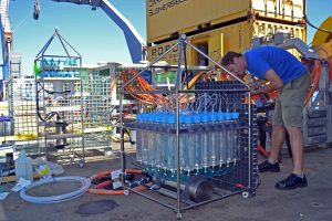 Giora Proskurowski, a Project Scientist with the UW RSN Team, prepares a Remote Access Fluid Sampler (front) and microbial DNA sampler for installation in a diffuse flow site at the vent called 'El Gordo' in the International District hydrothermal field. The instrument is designed by Dr. David Butterfiled and NOAA-PMEL and the UW. Image Credit: Mitch Elend, University of Washington; V14.