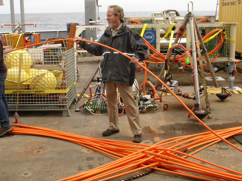 John Wonderly, a teacher from Clallam Bay School, assists with the respooling of 250 m of cable onto the ROCLS drum. This cable totals 4.7 km in length and will be laid on the seafloor to connect Axial Caldera's Primary Node PN3B with the Central Caldera Secondary Node. Photo Credit: Leslie Sautter, College of Charleston, V14.