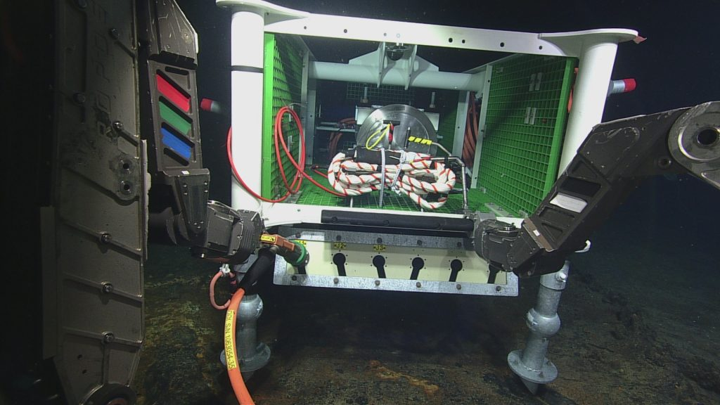 On July 20, the medium-powere junction box MJ03C was installed in the International District hydrothermal vent field on ROPOS Dive R1717. It was connected to a ~2300-m-long cable (RSO3W6) that will connect this system to Primary Node PN3B. A temperature-resistivty sensor (TRHPHA301) is inside the J-Box, awaiting installation during a follow-on dive. Photo credit: NSF-OOI/UW/CSSF; Dive 1717; V14.