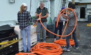 Dana Manalang and Eric Olsen (UW) work with UW students Gina Hansen and Don Setiawan to.prepare the end of a fiber optic cable segment so that it can be spooled by hand onto the large cable spool. The spool will then be transported by ROCLS for installation on the seafloor.  Photo credit:  Mitch Elend, University of Washington, V14.
