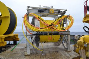 Cable RS03W4, a 1 km extension cable, sits on the ROPOS work platform awaiting attachment to ROCLS on the underbelly of the ROV ROPOS. Photo Credit: NSF-OOI/UW/CSSF; Dive R1715; V14.