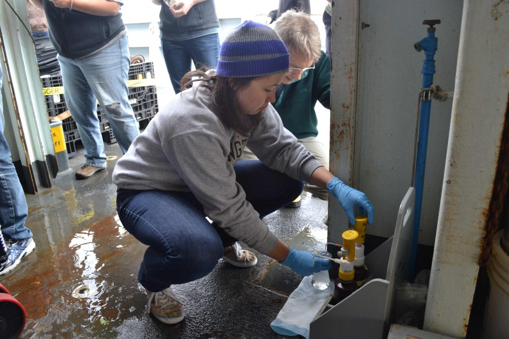 Gina Hansen, University of Washington Bioengineering student, helps takes water samples collected at ~ 9000 ft beneath the ocean's surface near Axial Seamount (volcano). Photo Credit: Mitch Elend, University of Washington, V14.