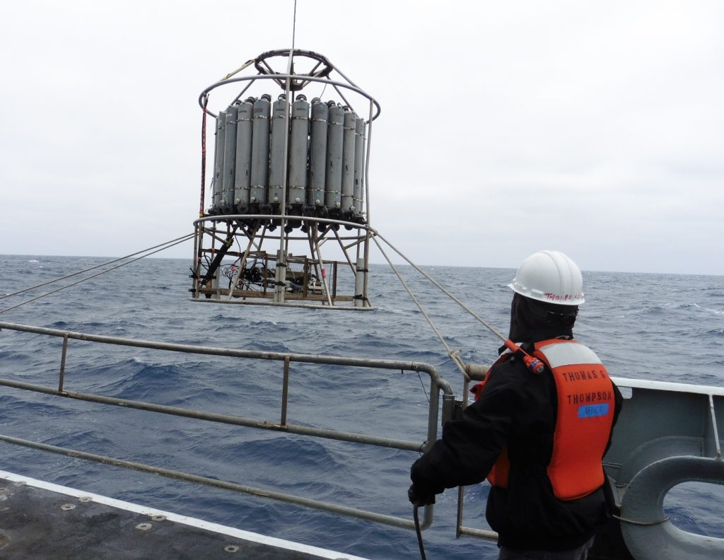 The CTD (Conductivity-Temperature-Depth sensor) is deployed into the ocean. All of the Niskin bottles are held open before deployment and are closed individually to collect water samples at different depths as the CTD carousel rises through the water column.  Photo credit: John Wonderly, Clallam Bay School, V14.