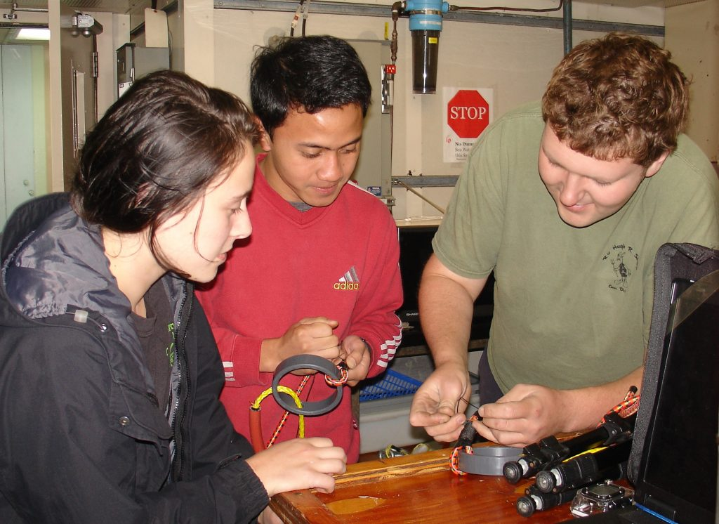 Ben Brand (Univ. of Washington) teaches UW students Don Setiawan and Krista Nunnally to prepare the bungie cords used to tie down the spooled cable's end to the outer part of the ROCLS frame. O-rings provide an easy grab for the ROV's manipulator arm. Photo credit: Leslie Sautter, College of Charleston, V14.