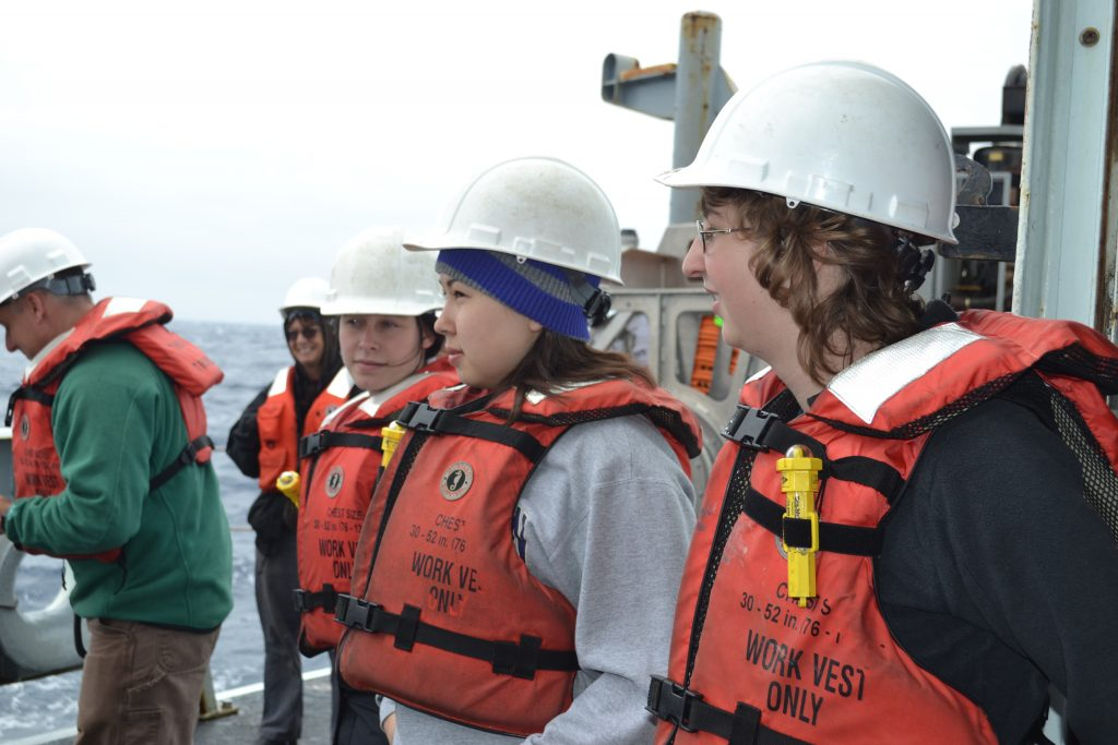 University of Washington, School of Oceanography students watch the first CTD operation on the R/V Thompson. Here, they learn how to safely handle lines, sample ocean water, and conduct analyes onboard once the CTD returns to the deck. Photo Credit: Mitch Elend, University of Washington, V14.