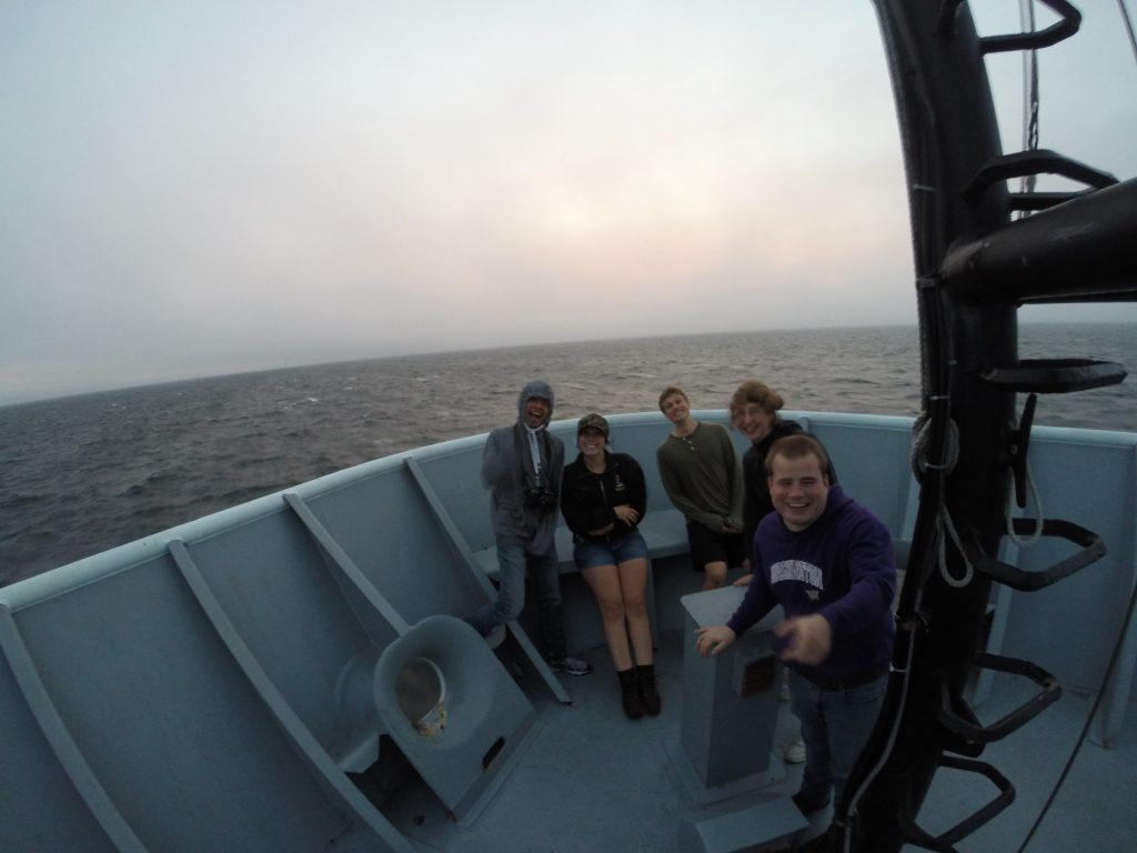 University of Washington students from Leg 1 brave the cold wind, rain and rough seas while on the bow's deck of the R/V Thomas G. Thompson, Leg 1 of VISIONS '14. Photo credit: Christina Ramirez, University of Washington, V14.