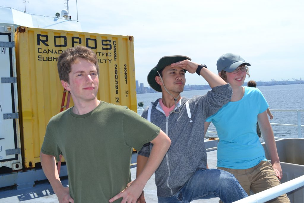 Sam Albertson, Don Setiawan, and Katie Bigham look out to the west, awaiting the departure of the R/V Thompson from Seattle. Photo Credit: Mitch Elend, University of Washington V14.