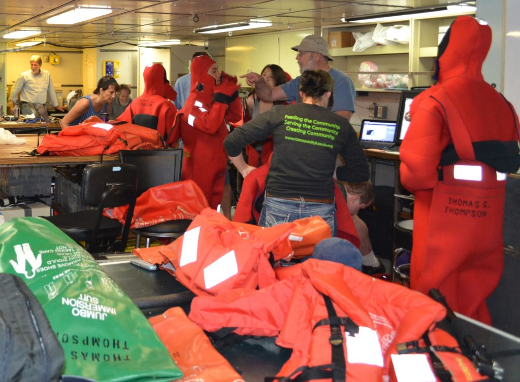"As part of the safety drills, all participants must practice getting into the thick orange rubber immersion suits, also called ""Gumby Suits."" Photo credit: Mitch Elend, University of Washington, V14."