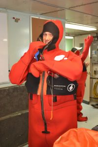 "University of Washington, School of Oceanography undergraduate, Jesse Turner, practises getting into a ""gumby"" suit during a safety meeting onboard the R/ V Thomas G. Thompson. Photo Credit: Mitch Elend, University of Washington, V14."
