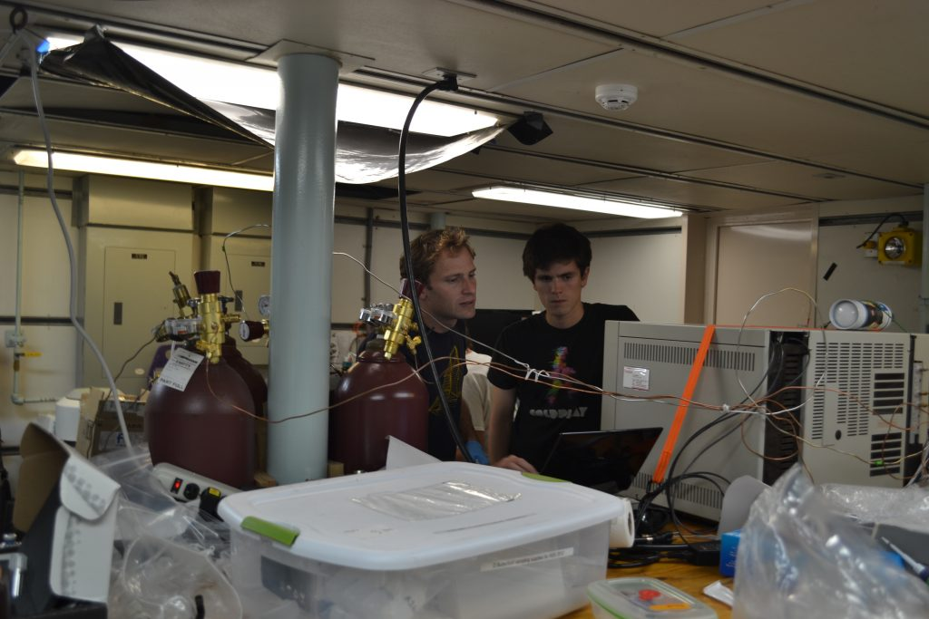 Brendan and Giora analyze gases in hydrothermal fluids from the chimneys called 'Diva' and 'Escargo' in the International District Hydrothermal Field on Axial Volcano. The fluids are sampled using highly specialized tiranium water samplers to collect 'gas tight' samples, and analyzed onboard the Thompson using a gas chromatograph. Photo Credit: Deborah Kelley, University of Washington.