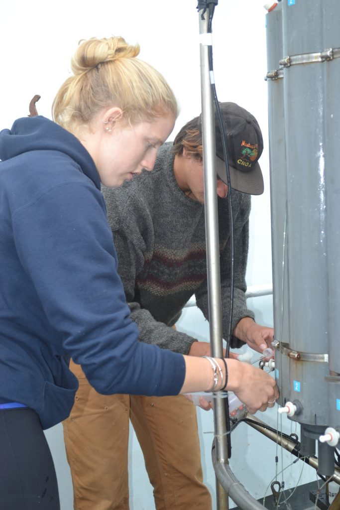 Caitlin and Andrew take water samples from a CTD cast ~ 125 km off the coast of Oregon to characterize fluids up to 9000 ft beneath the oceans surface.