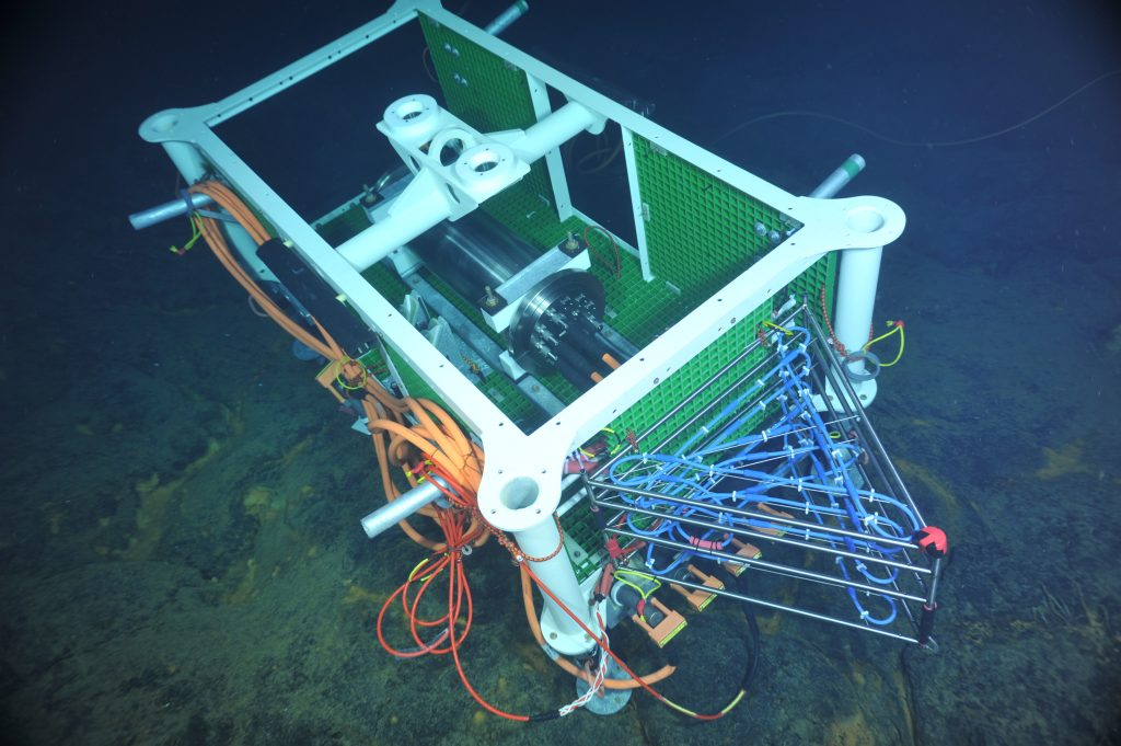 The 3D thermistor array designed by RSN Project Scientist Giora Proskurowski is attached to the Medium Powered J-BOx (MJ03B) in the ASHES hydrothermal field. The array will be tested on a follow-on dive, and in 2014 it will be deloyed in a diffuse flow site at the base of the vent called Mushroom, along with a high-definition video camera and an osmo vent fluid sampler. VISIONS '13, Leg 4    Photo credit: NSF-OOI/UW/CSSF.