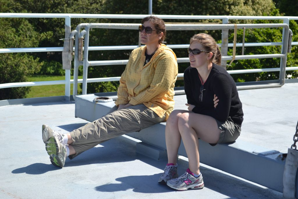 Julie Ann and Claire sit on the upper deck of the R/V Thompson as it goes through the Ballard locks on Leg 1 of VISIONS'13.