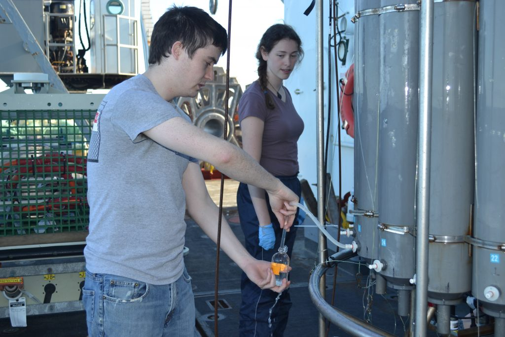 Owen Coyle showing student Adrian Rembold how to collect water samples during VISIONS'13, Leg 2. Photo by Mitchell Elend