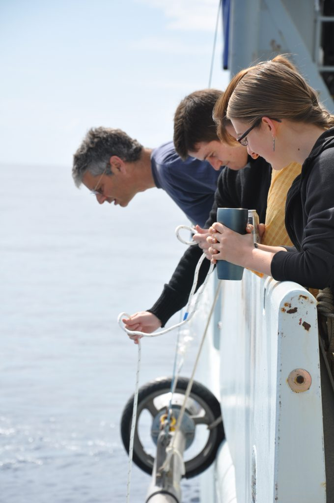 Claire looks on as Owen and Danny use a buckets to scoop up salps from the ship. Photo by Judy Twedt