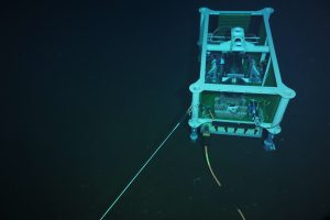 The medium powered Junction Box (MJ01A) is connected to > 1800 feet of extension cable deployed by ROPOS on the seafloor at the base of Axial Seamount. A pressure sensor inside the node is awaiting deployment for follow-on testing.  	Photo credit: NSF-OOI/UW/CSSF