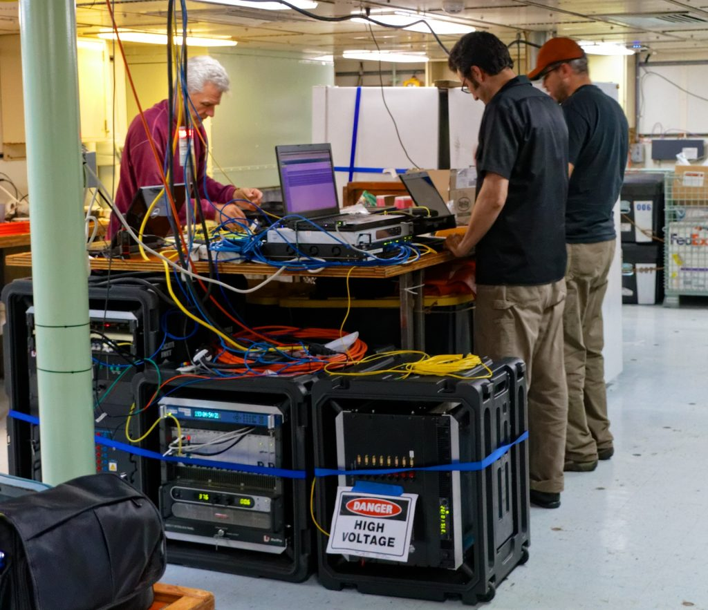 Applied Physics Lab engineers (from left to right) Tim McGinnis, Jesse Dosher, and James Tilley look over tests results as ROPOS connects to a secondary node on the seafloor and sends real-time data back to the surface. Photo by Ed McNichol