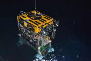 ROPOS goes into the water in the early morning of July 10, prior to descending 2600 m (~7800 ft) to the seafloor. Directly latched below the vehicle is the medium-powered junction box, MJ01A.  	Photo credit: NSF-OOI/UW/CSSF