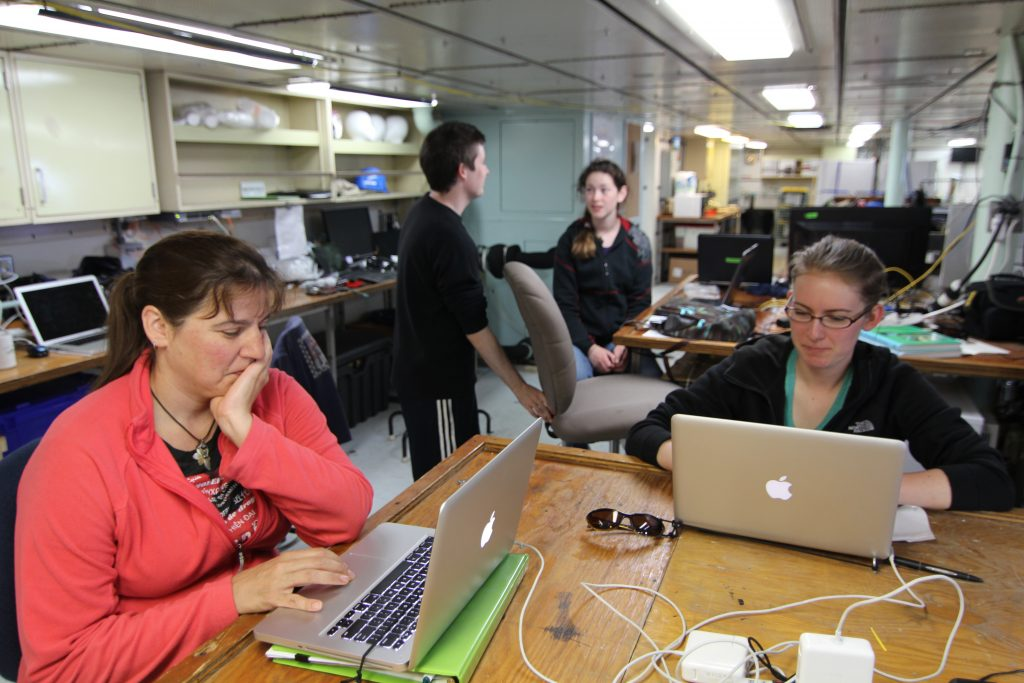Students Julie Ann Koehlinger, Claire Knox (left to right), Owen Coyle, and Adrian Rembold (background) in the main lab during the transit out of Newport. (photo: Allison Fundis)
