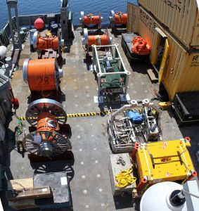 Drums holding extension cables and a secondary node are loaded onto the fantail of the R/V Thompson in preparation for deployment. Photo by Skip Denny.