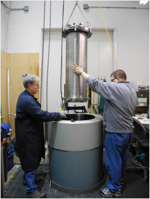 Figure 3. Randy Fabro and Larry Nielson lowering a housing into the UW School of Oceanography Pressure Test Vessel.  --Photo by Geoff Cram