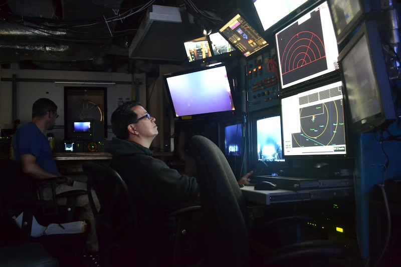 ROPOS pilot Jonathan Lee controls the ROV as it begins its descent down through the water column. APL-UW engineer James Tilley operates the HD camera in the background. (photo by Mitch Elend)