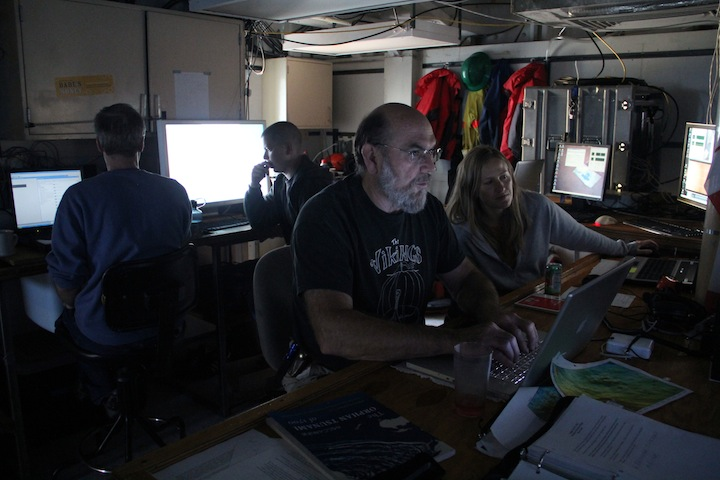 Skip Denny and Dana Manalang log events during their 4 hour watch in the ROPOS control room. Mitch Elend and Monica Riess (back) work to stich together images into a photomosaic as they come in from the digital still camera mounted on the ROV. (photo by Allison Fundis)