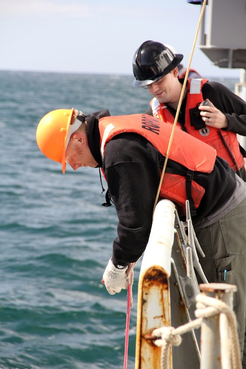 Josh Chernoy and Vincent Auger of the ROPOS crew secure the USBL pole that is used to navigate the ROV. (photo by Allison Fundis)