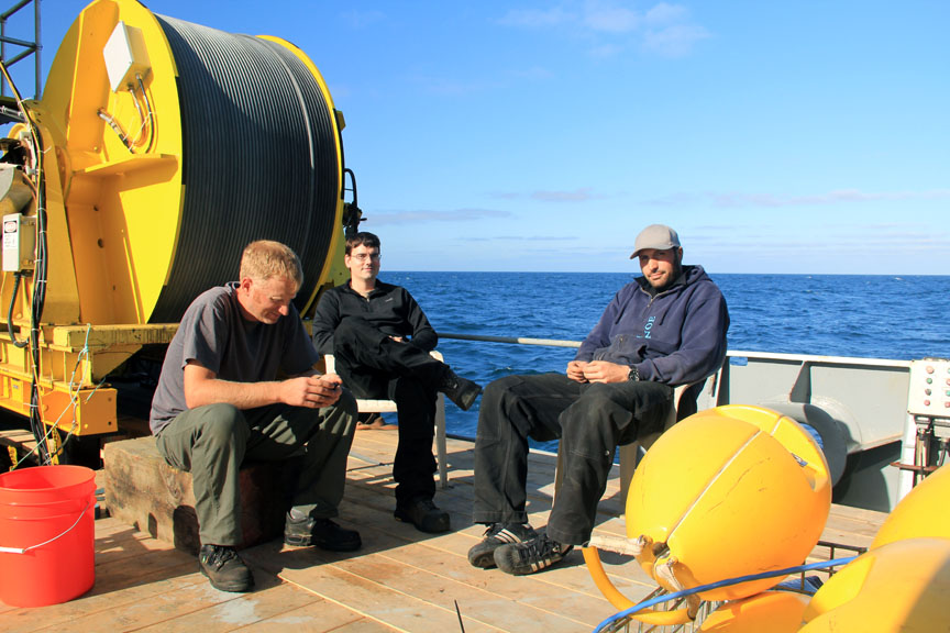 Members of the ROPOS crew (Josh Chernoy, Vincent Auger, and Reuben Mills) take a break after spending the entire night reconfiguring the components on the ROV to be setup for down-looking mosaics. (photo by Allison Fundis)