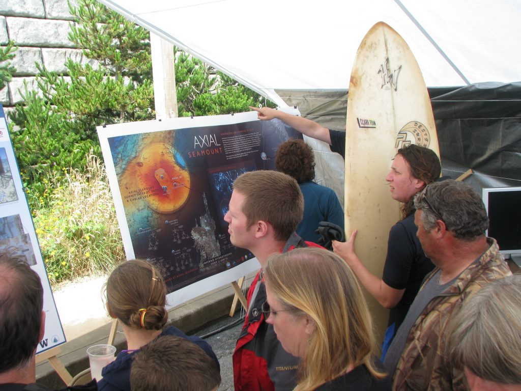A surfer takes a break and checks out the OOI Dory Days booth along with other visitors.  --Photo courtesy of David Muerdter