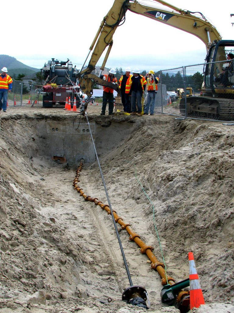 Work site at beach manhole in Pacific City for second cable landing, July 15, 2011. Note first cable, landed July 12, 2011, is shown encased in split pipe.