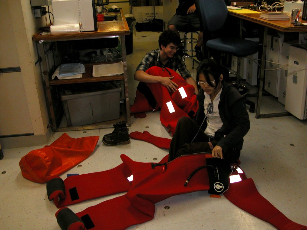 Mark and En practice getting into their Gumby suits during the safety meeting prior to transiting to Axial Volcano.