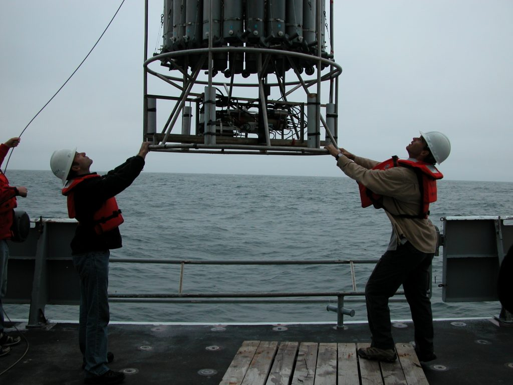 Chris (left) and Gregg (right) show the students how to put the CTD over the side the first day at sea.