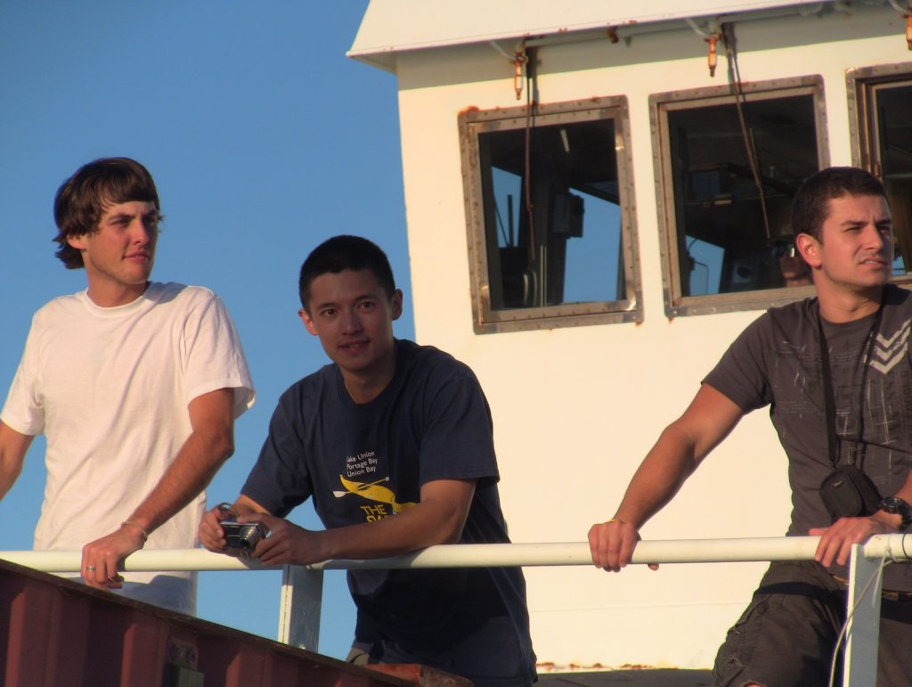 Sam, Likhi and Derek gazing from out towards the locks from the deck of the R/V Thompson