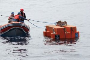 UW-APL engineers Trina and Chris use the small boat from the R/V Atlantis to attach the retrieval line onto the Shallow Profiler Mooring platform