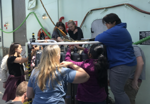 VISIONS19 students become familiar with the CTD in preparation for an upcoming cast to collect ocean water. Credit: M. Vadaro, UW, V19.