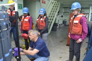 Co-Chief Scientist, Orest Kawaka, mentors Leg 2 VISIONS'19 students in sampling of ocean water from the CTD. Credit. M. Elend, University of Washington.