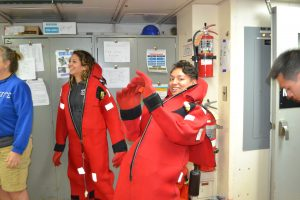 Eve Hudson dons her survival suit as part of the Leg 3, Day 1 safety briefing on R/V Atlantis. Credit: M. Elend, University of Washington, V19