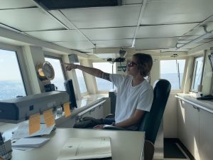 Recent UW graduate and new employee Rachel Scott on the bridge of the R/V Atlantis during the VISIONS '19 cruise. Credit: R. Scott, V19